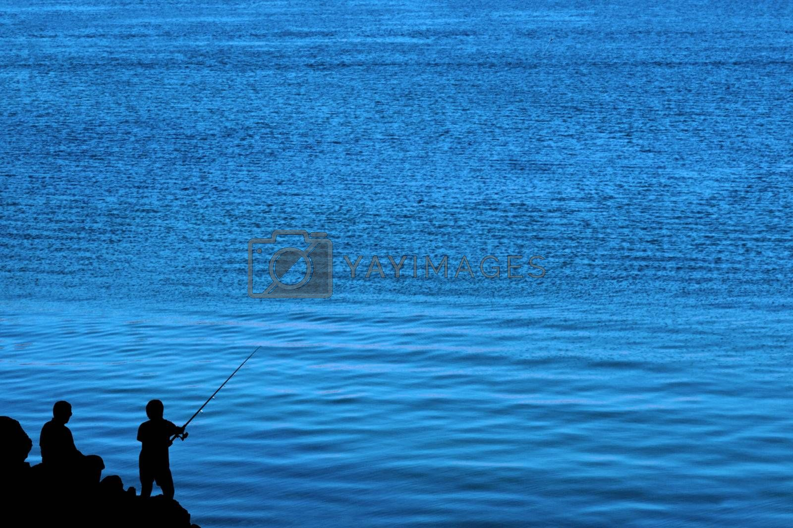 a silhouette of a father and son fishing of the rocks in ireland