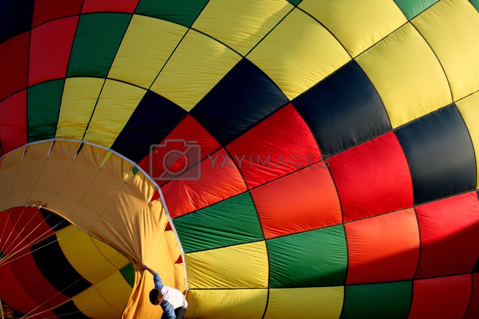 Young boy holding open a hot air balloon taking on some air