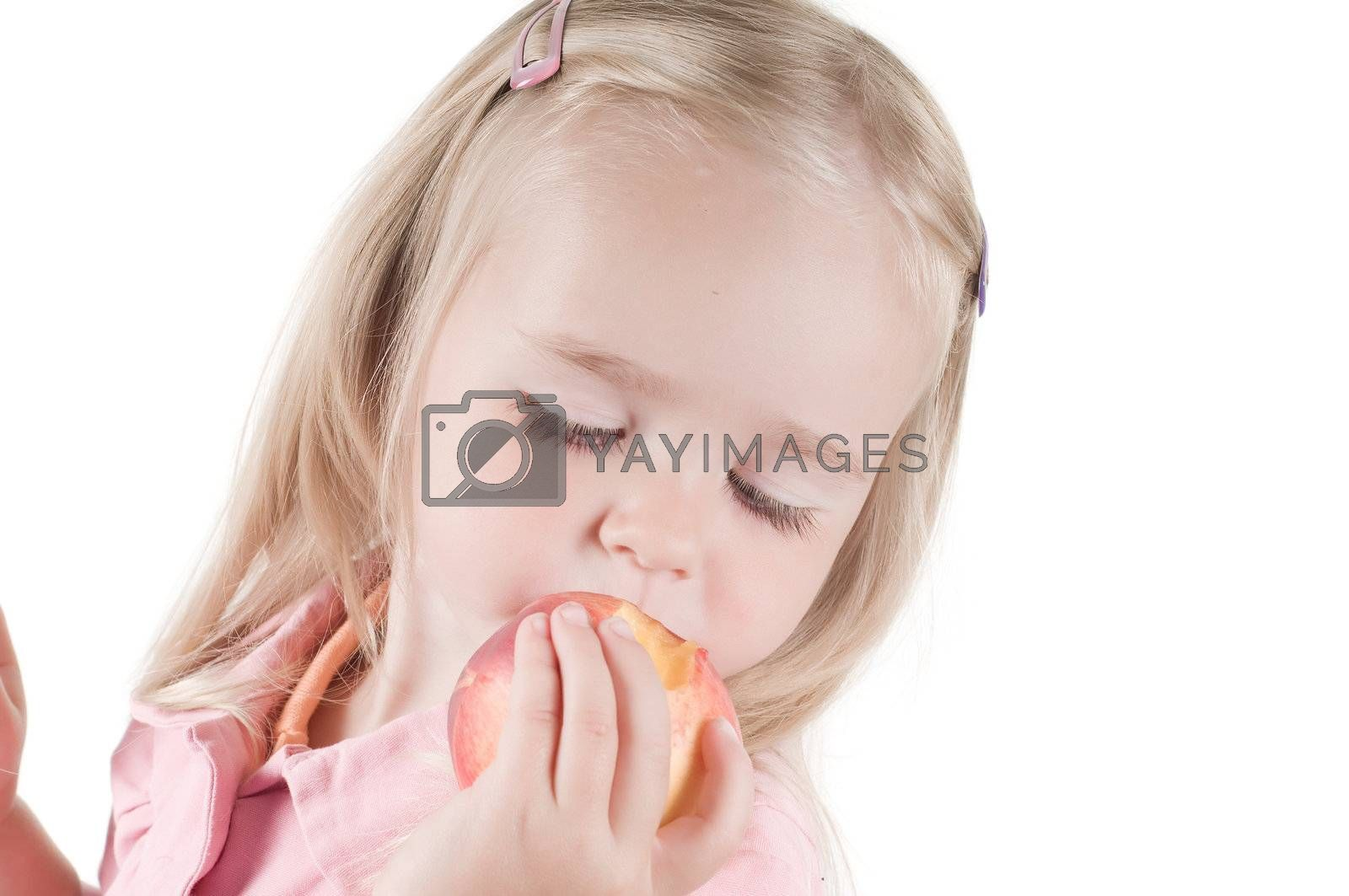 Royalty free image of Little girl eating peach in studio by anytka