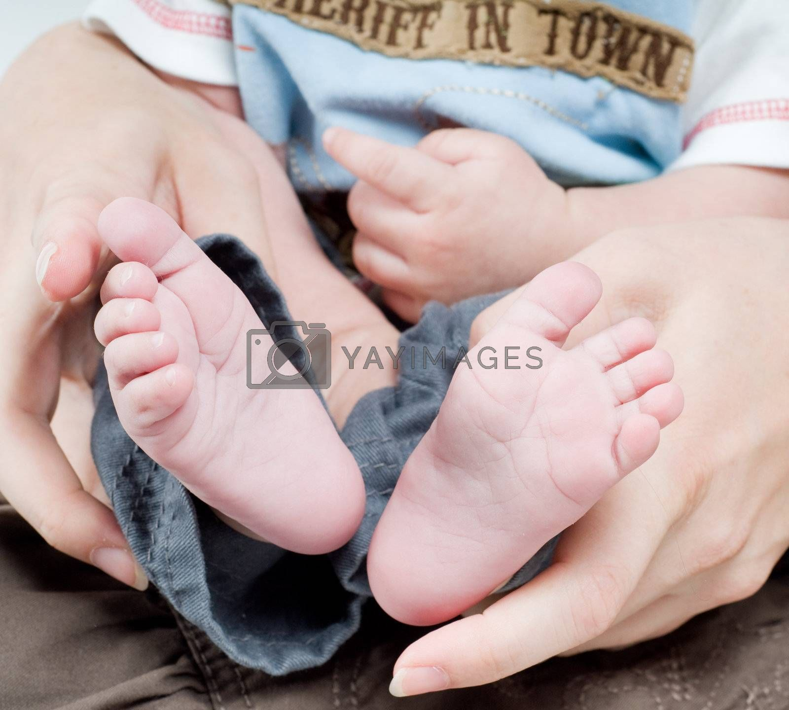Royalty free image of Newborn child in caring hands by anytka