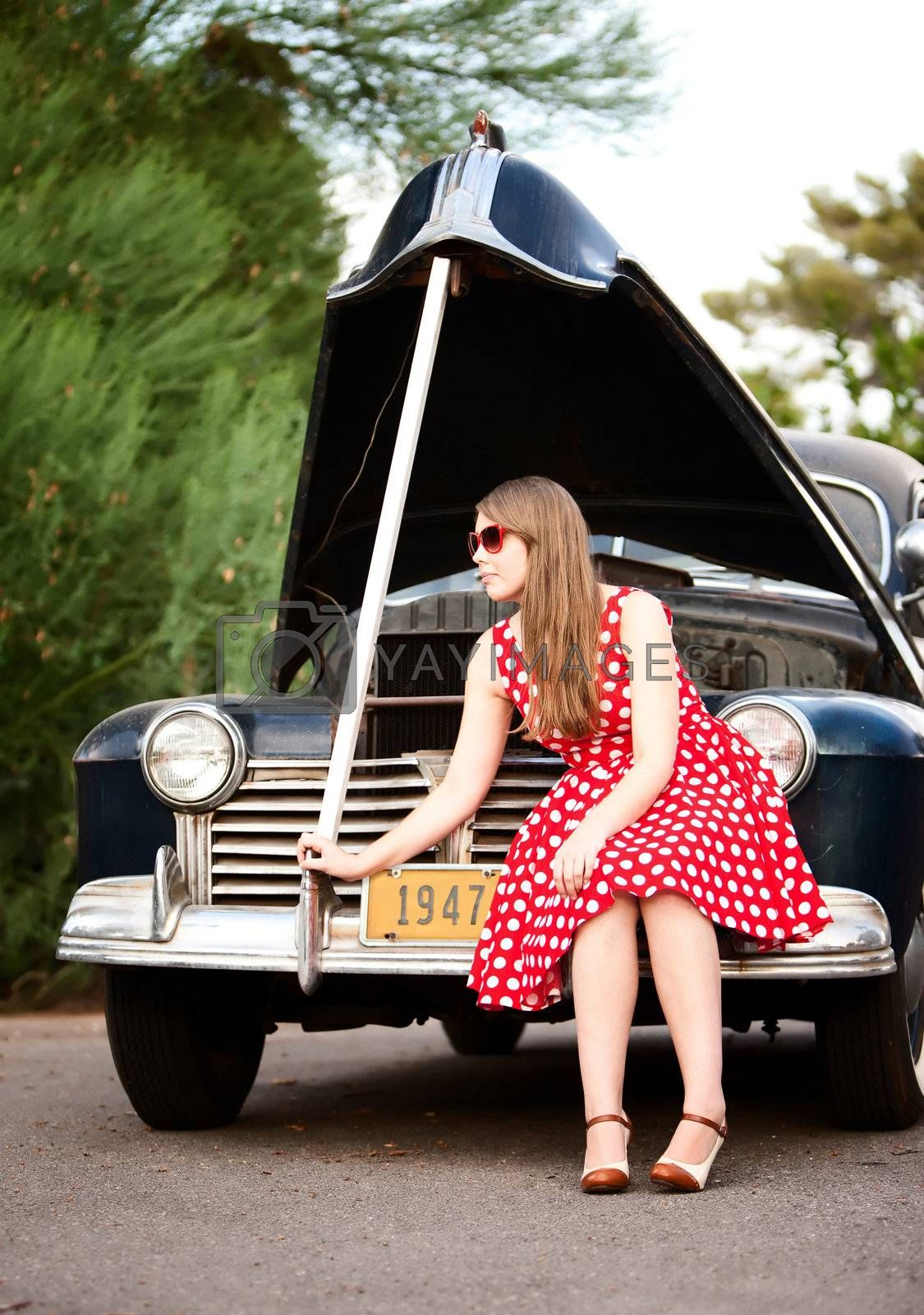 Royalty free image of Girl in red with vintage car by Creatista