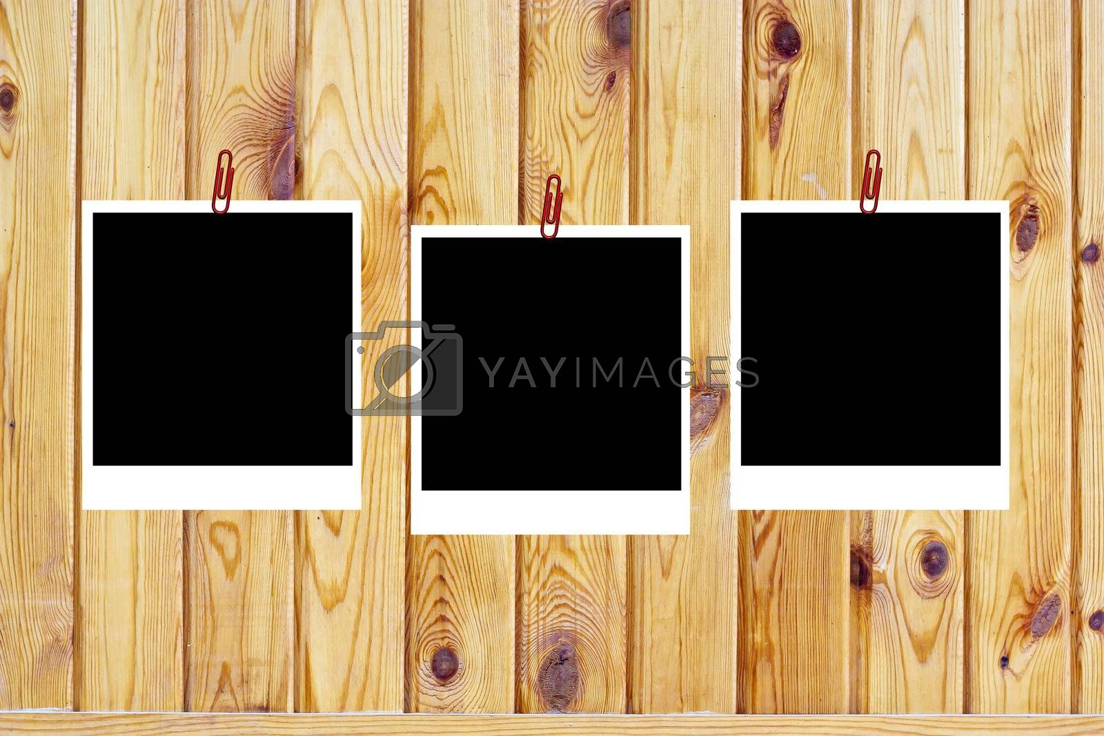 set of three old blank polaroids frames lying on a wood surface  by schankz