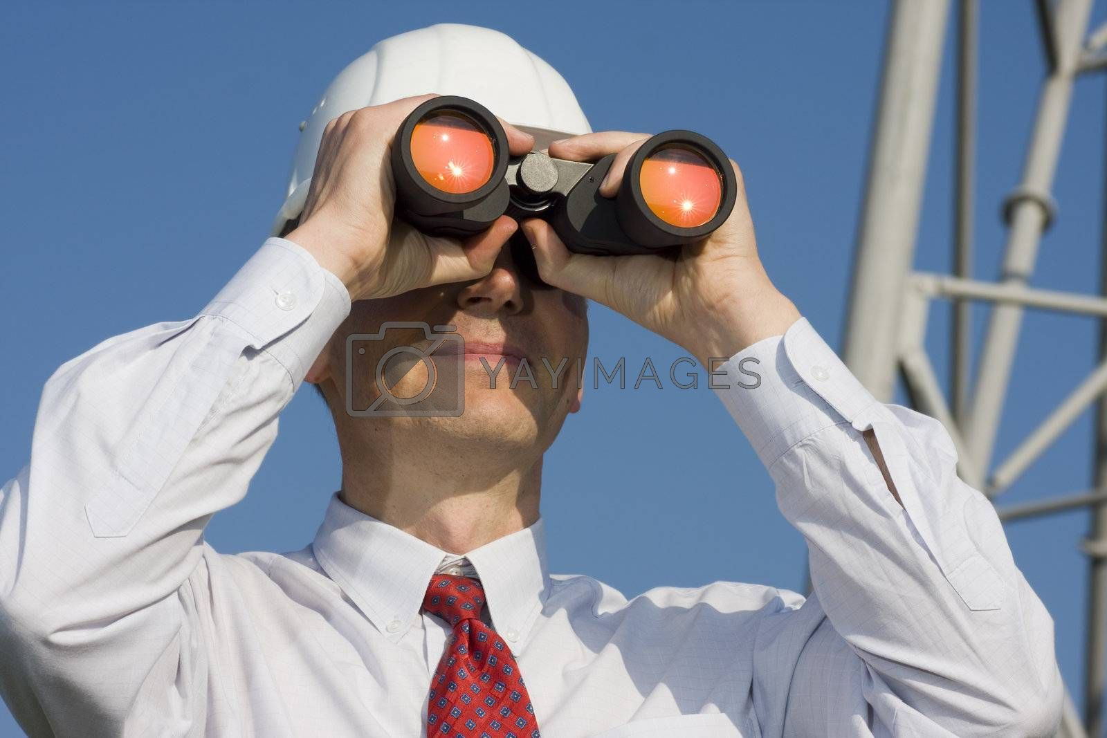 Engineer with binoculars on construction site