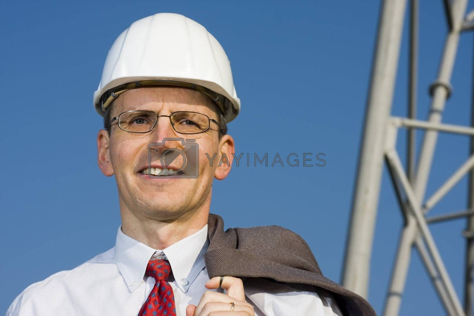 Smiling engineer in front of steel construction
