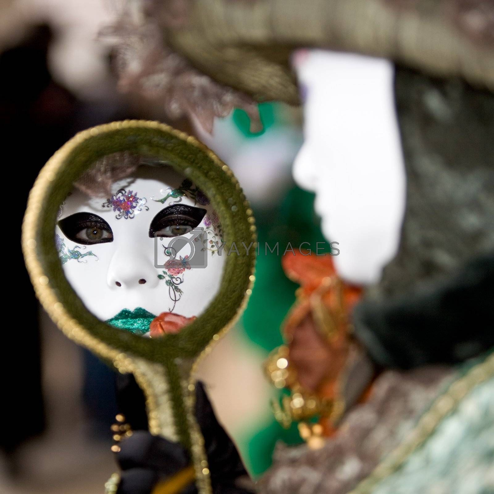 A woman with a venetian mask looking into a mirror