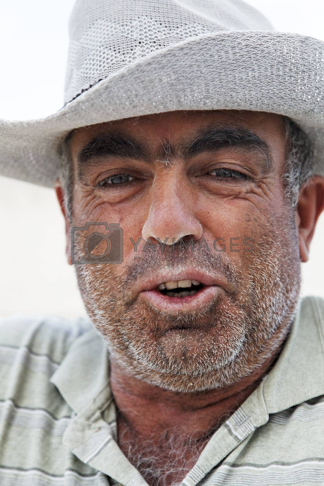 Goreme, Turkey - June, 2011: Portrait of weather beaten unshaven face of a senior gent Turkish builder with a dusty tanned face wearing a wide rimmed hat for protection against the sun, vertical close crop
