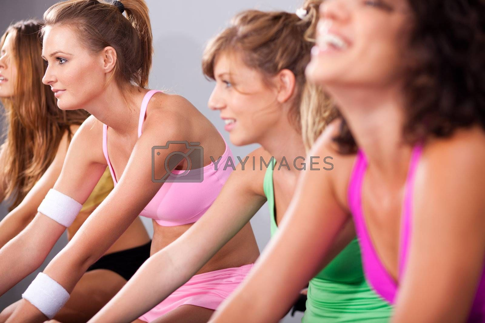 Group of four people spinning in gym or fitness club exercising their legs doing cardio training.