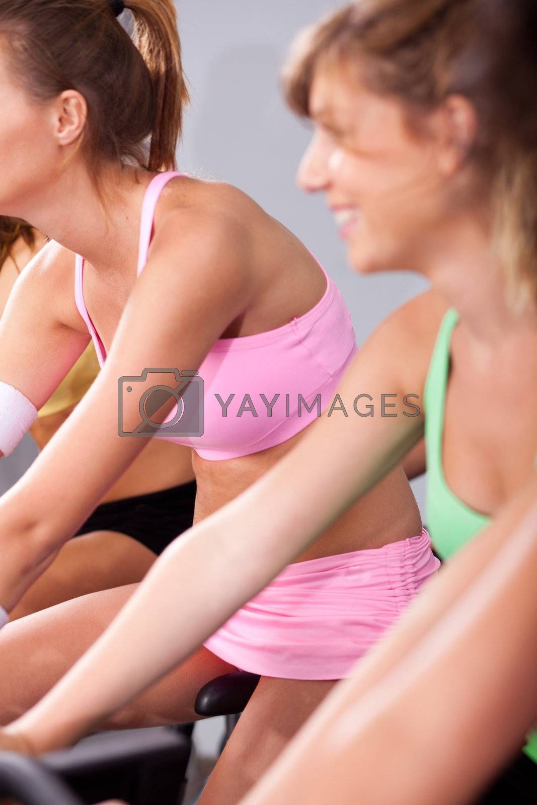 Group of people in a gym, cycling and keeping fit.