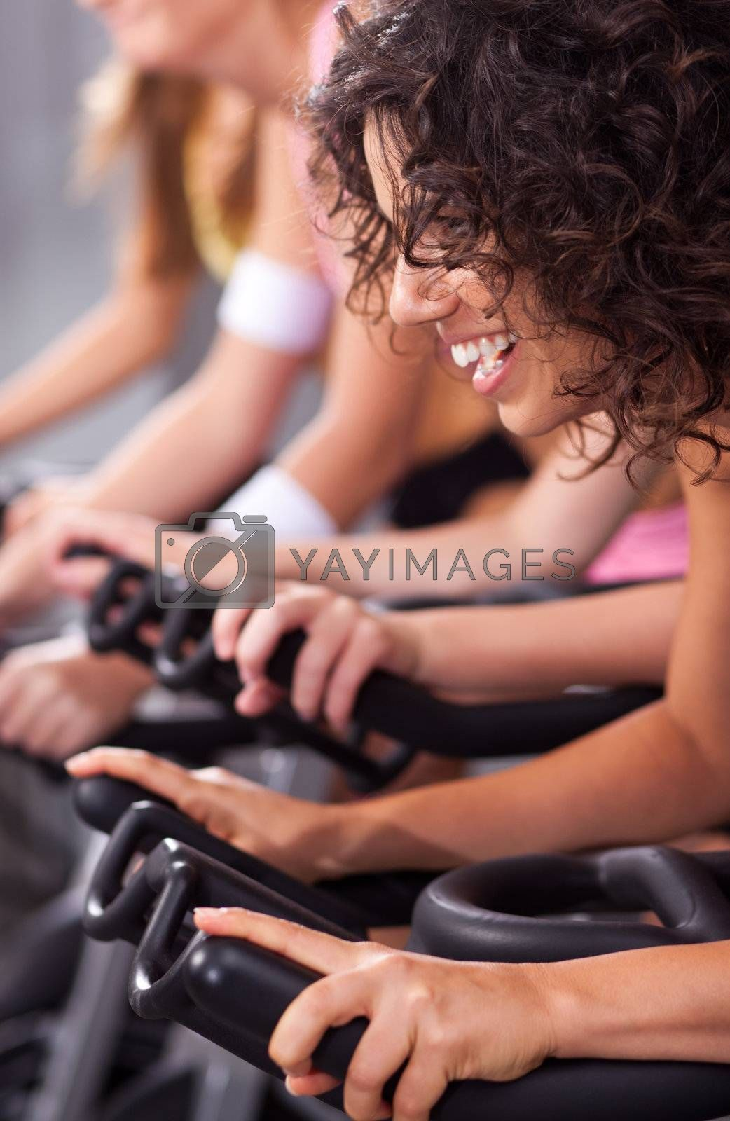 Four people on bicycles in a gym or fitness club for a workout.