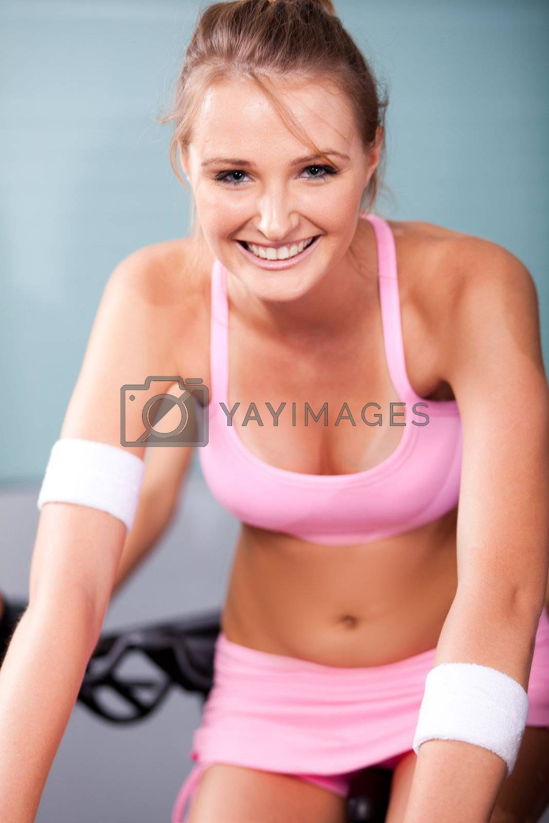Young woman smiling while doing cardio exercise in a gym.
