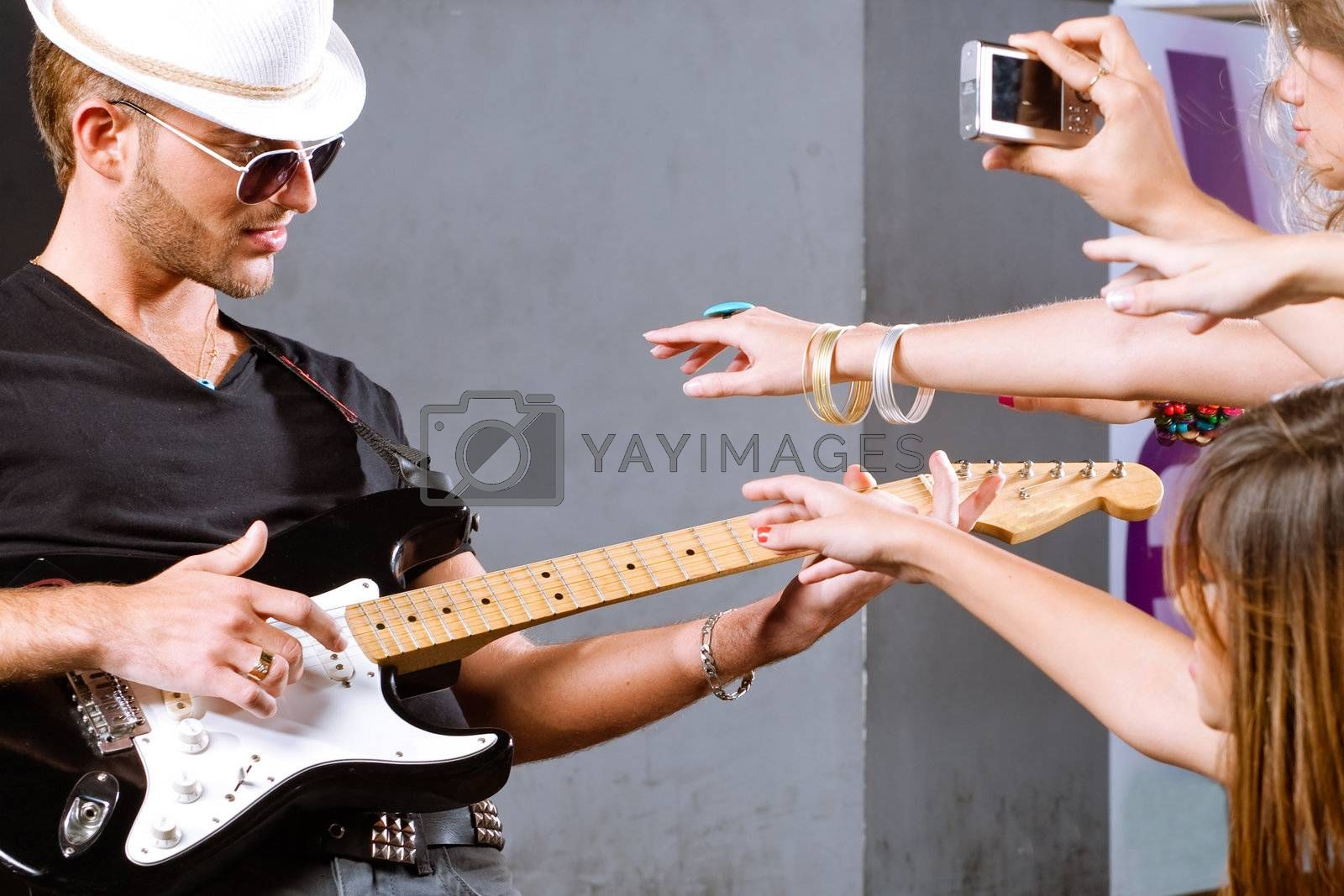Selective focus on guitar player with fans around.