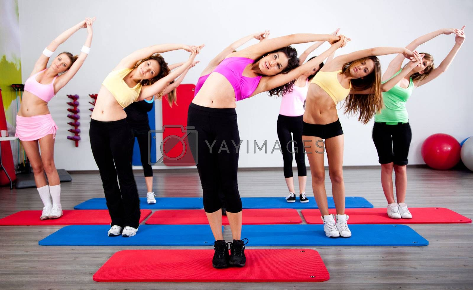 Group of gym people in a stretching class.