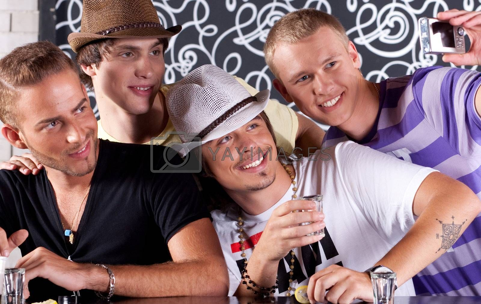Self portrait of handsome bunch of guys drinking and enjoying in nighclub.