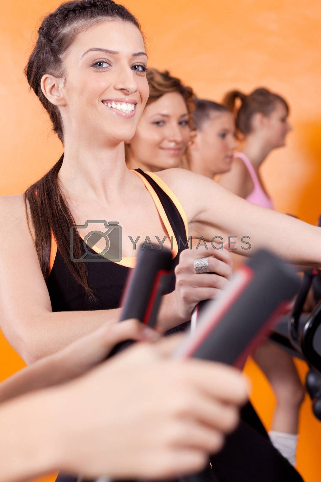 Group of four people in the gym, exercising their legs doing cardio training.