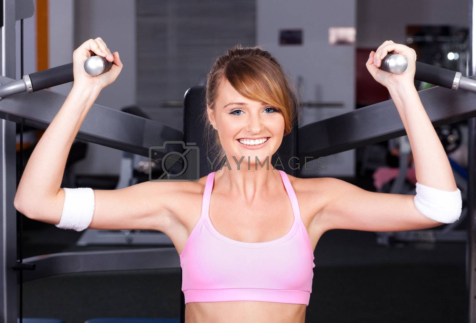 Beautiful woman at the gym, exercising...