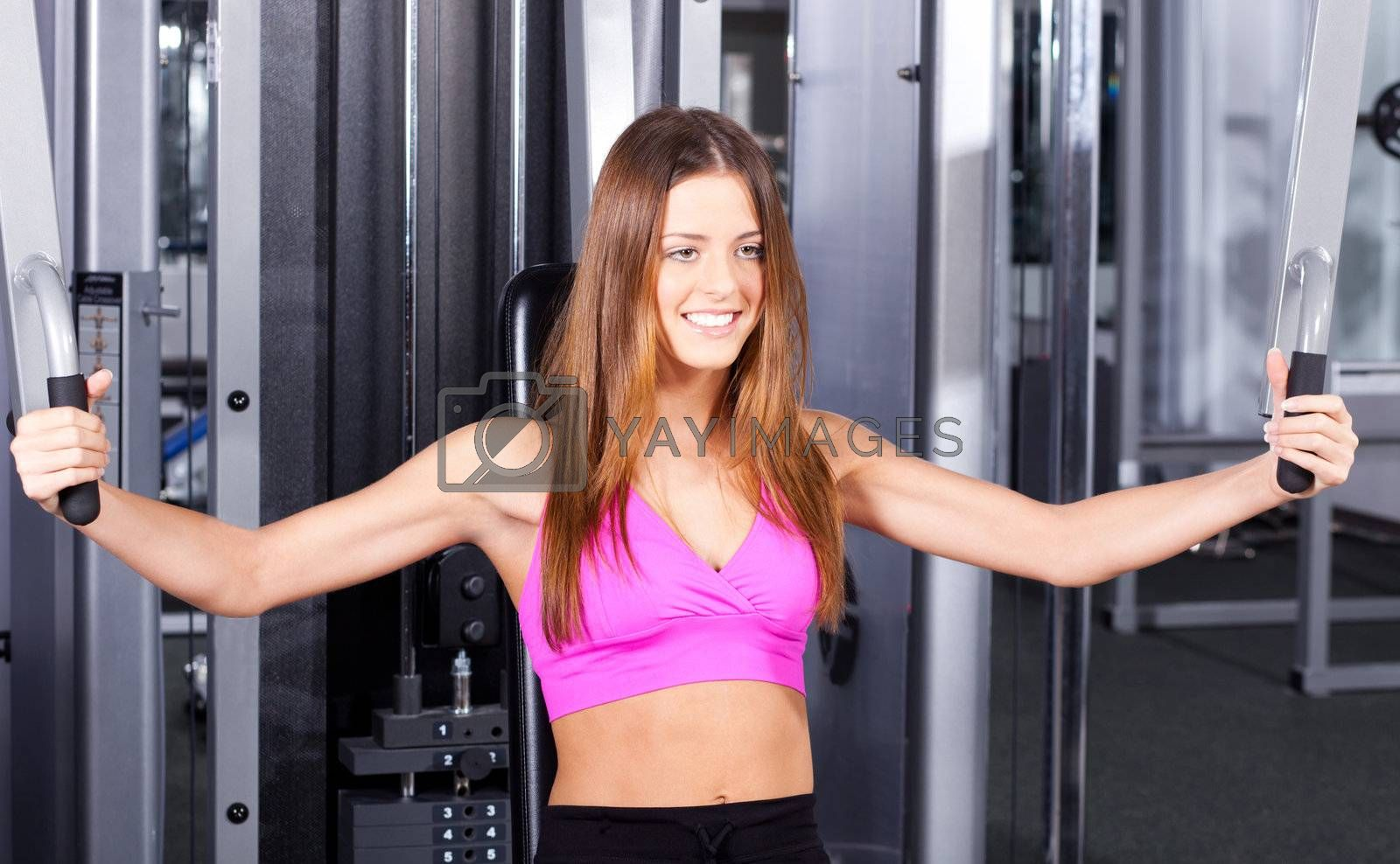 Health club: Fit girl in a gym exercising...