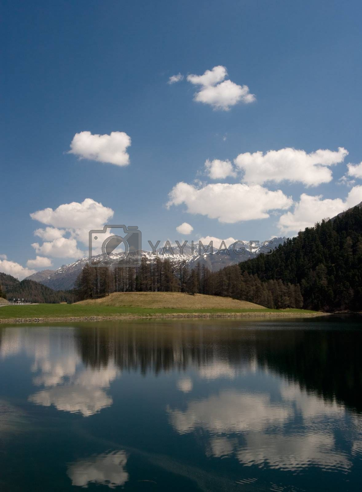 Lake reflection on a beautiful spring day, in the Swiss Alps. Silvaplana / Saint Moritz, Switzerland.