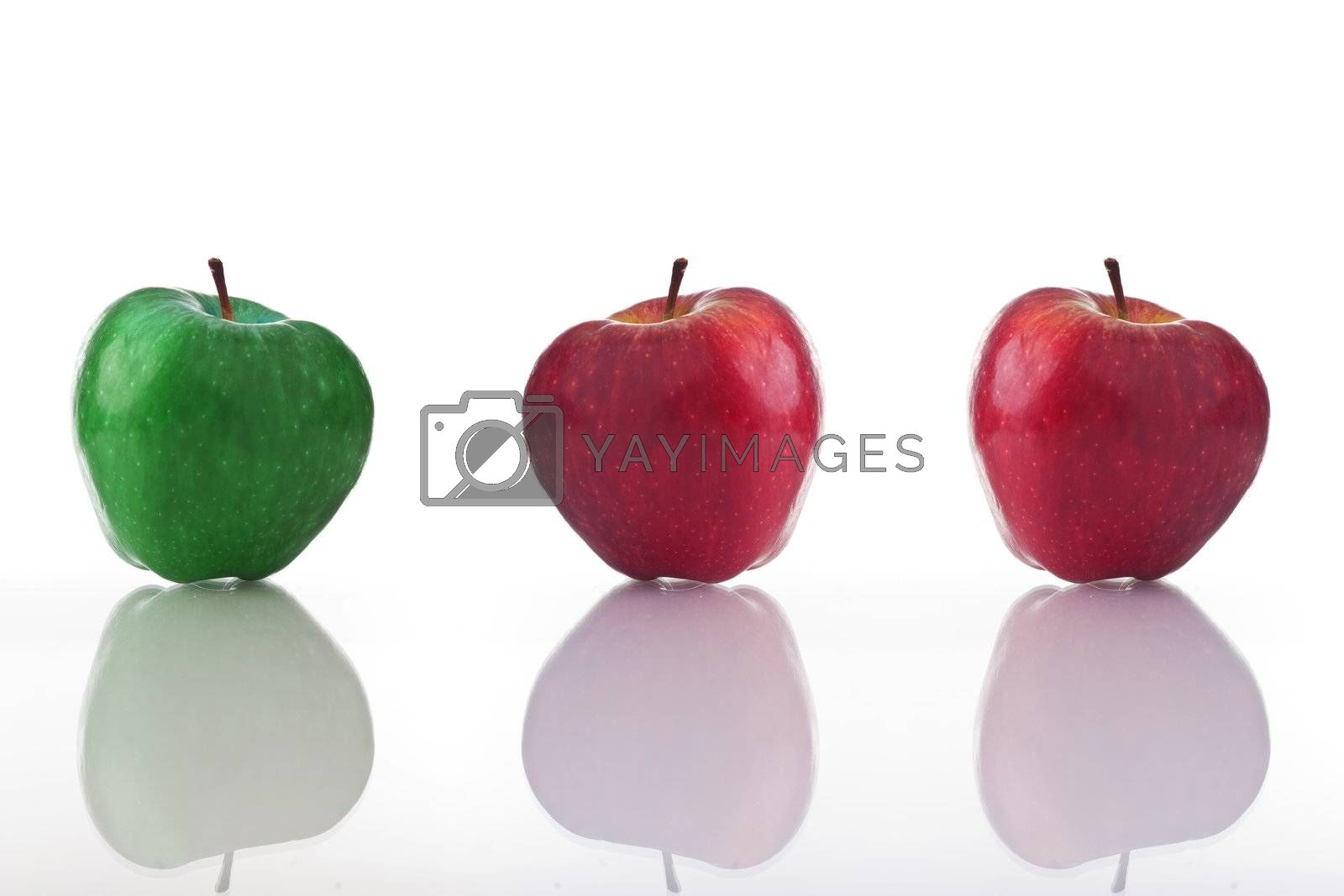 Three apples, one green and two red, isolated on white with reflection.