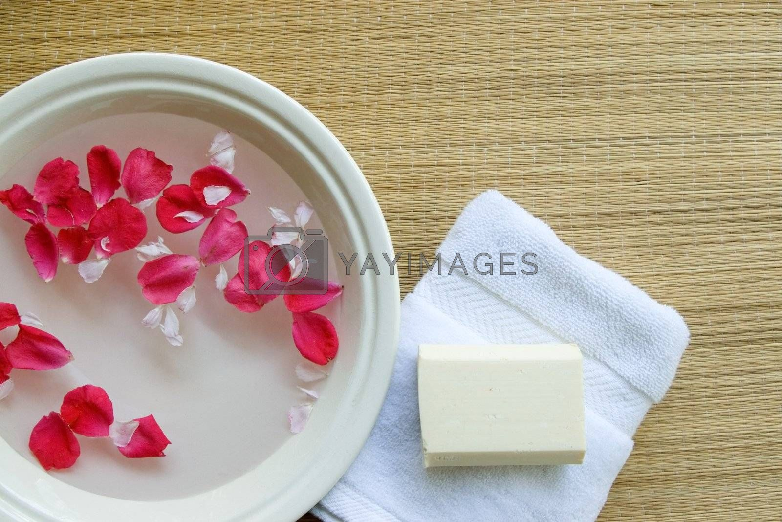 Minimalistic spa setting with floating rose petals, fluffy white towel, and all-natural soap bar.