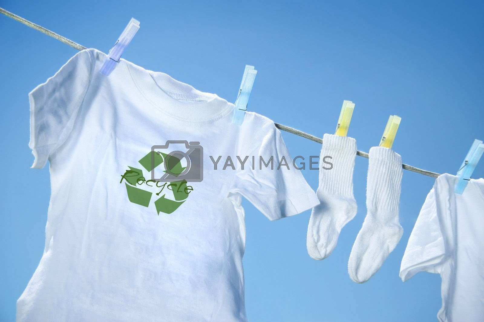 T-shirt with recycle logo drying on clothesline on a  summer day by Sandralise