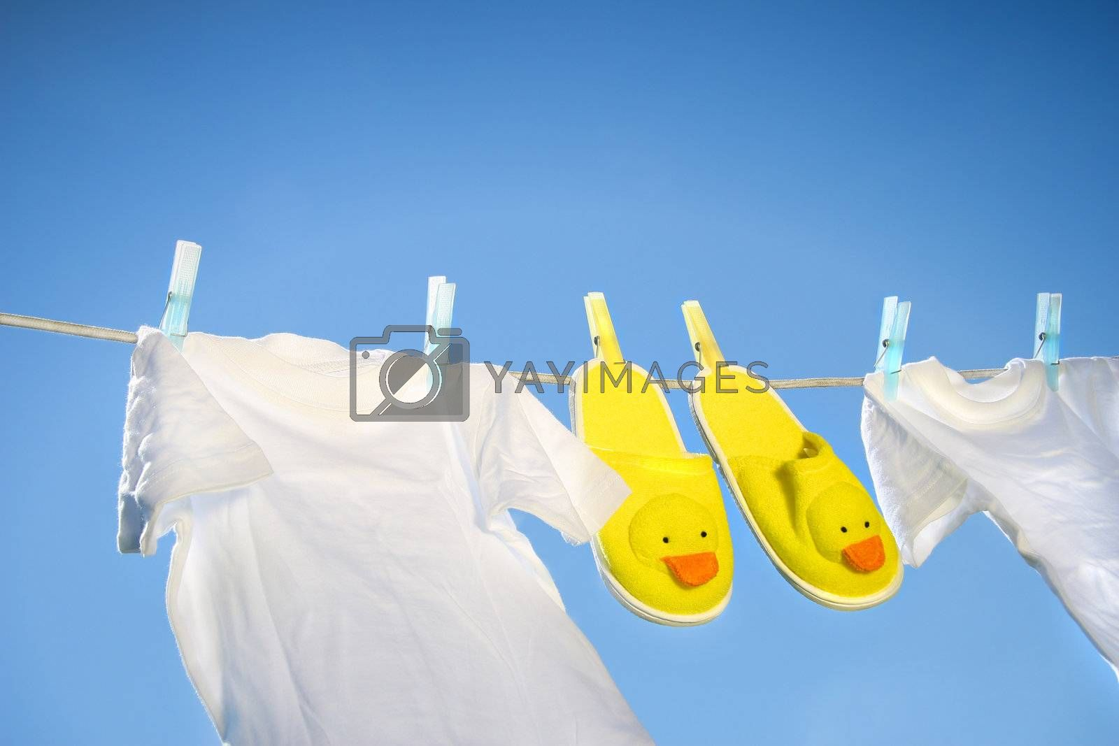 White t-shirts and slippers on the clothesline by Sandralise