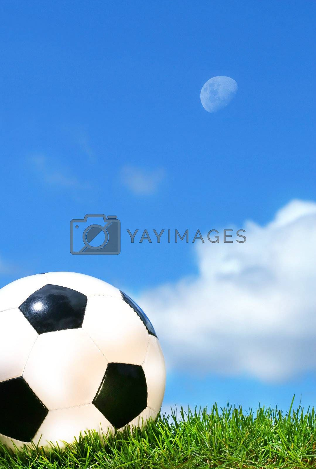 Closeup of a soccerball against a blue sky by Sandralise