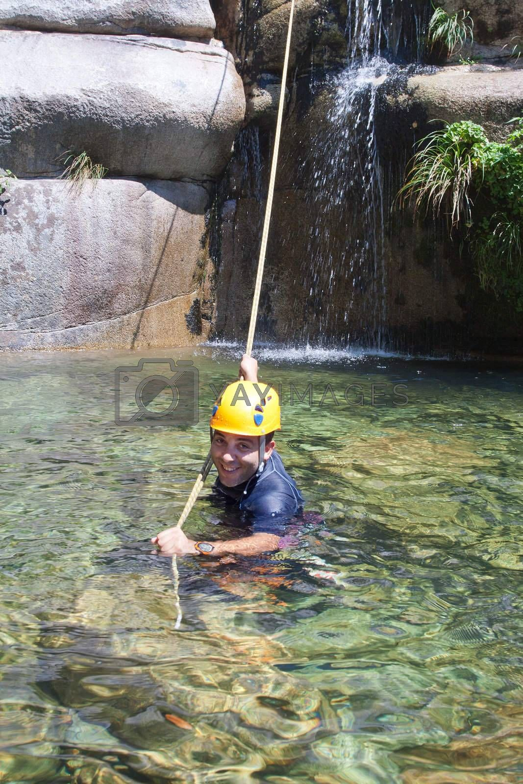 Men in the water pulling the rapel rope after descending