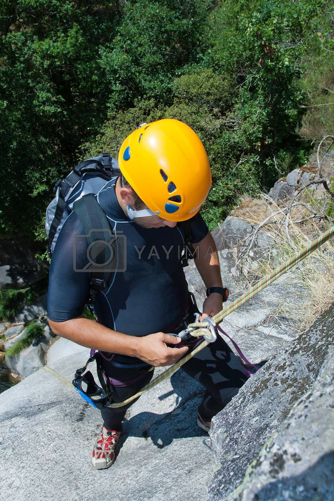 Men prepering to rappeling on waterfall checking is safe line and securety