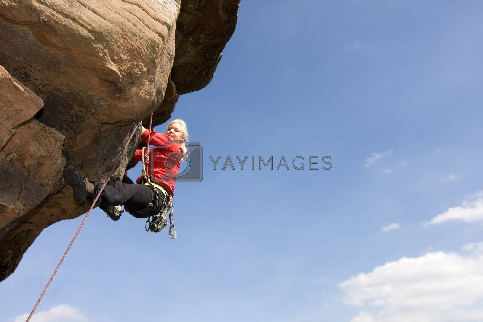 Young smiling woman climbing a sandstone rock