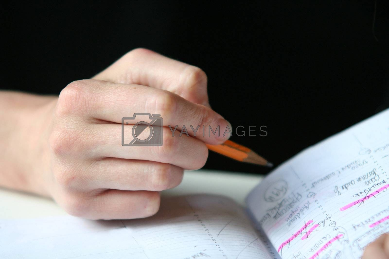 Girl's hand with pencil and notebook