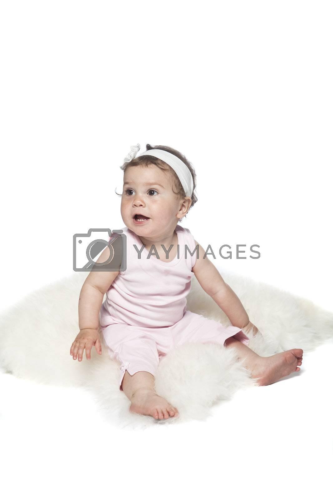 Baby sitting on a sheepskin isolated on white
