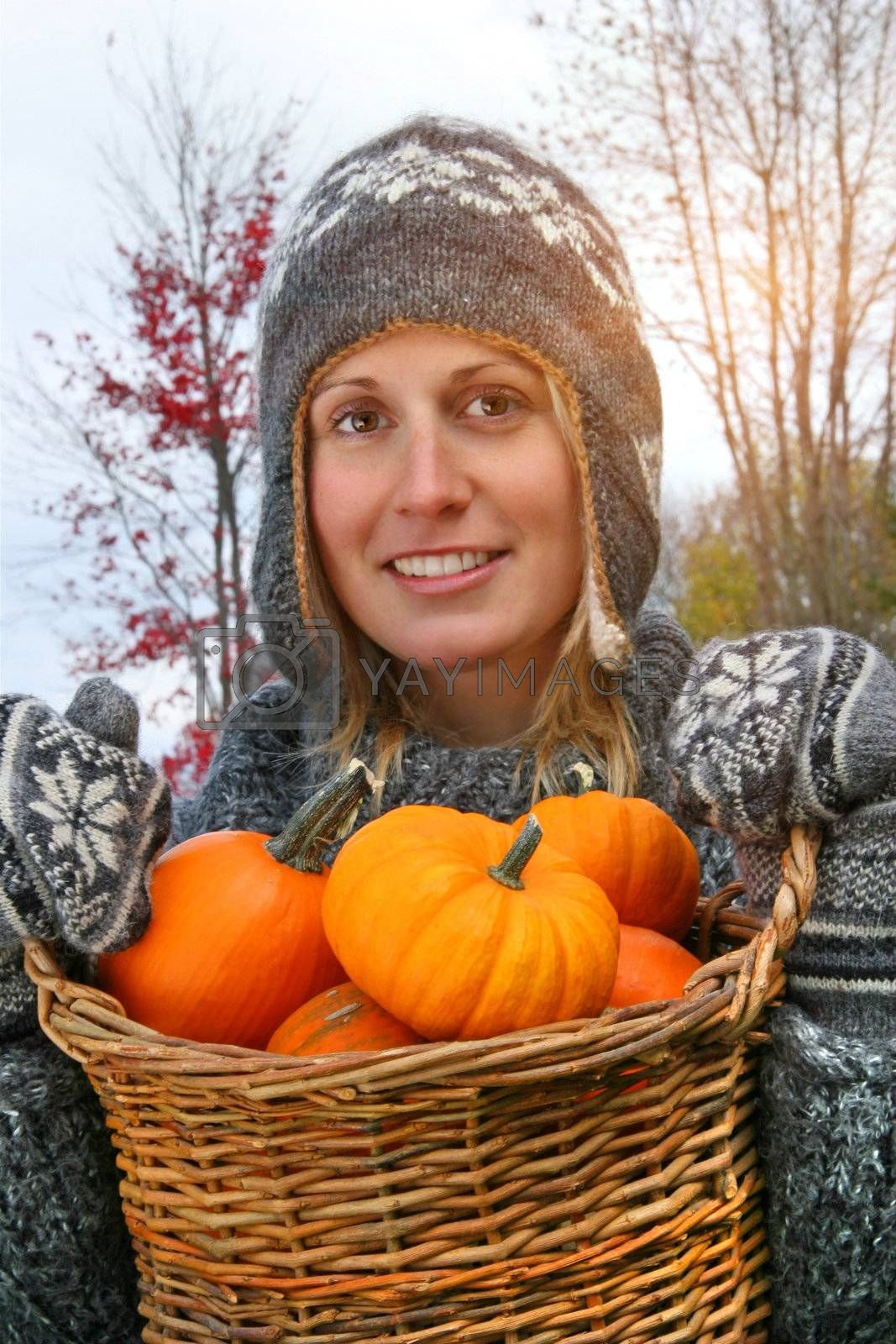 Young woman holding a basket full of small pumpkins