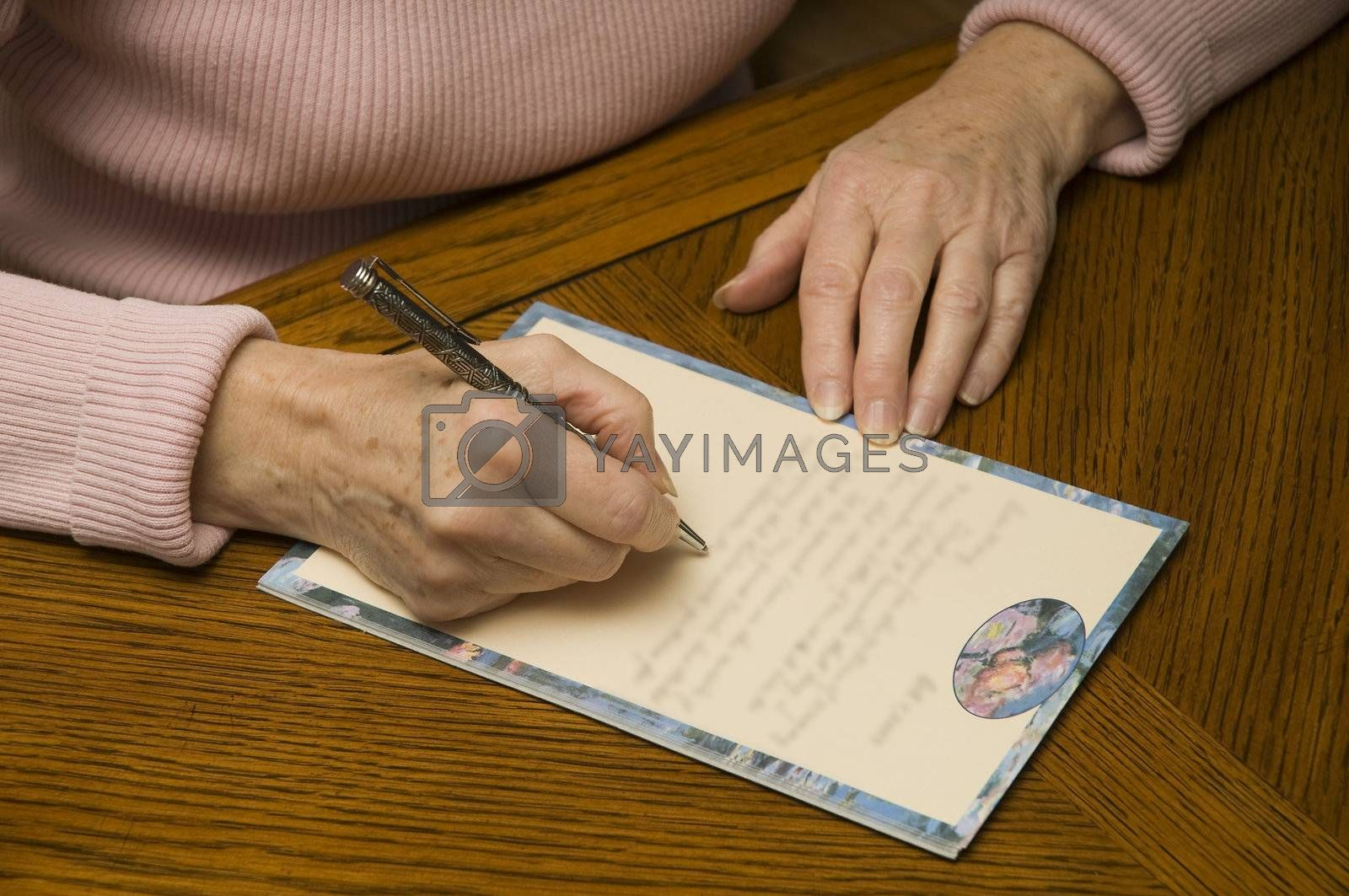an older woman writing a letter with a pen and paper