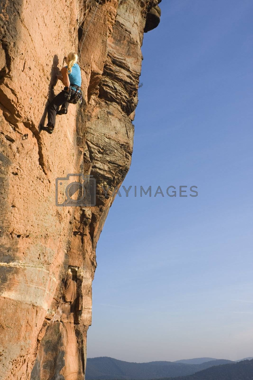 Young woman climbing by ArtmannWitte