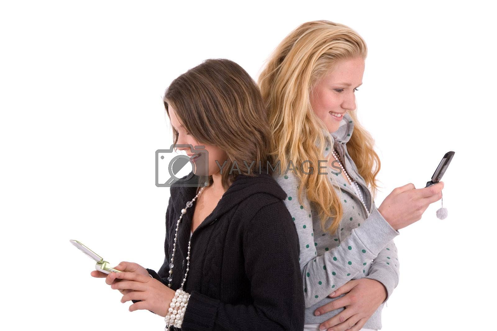 Two teenage girls standing side by side sending text messages