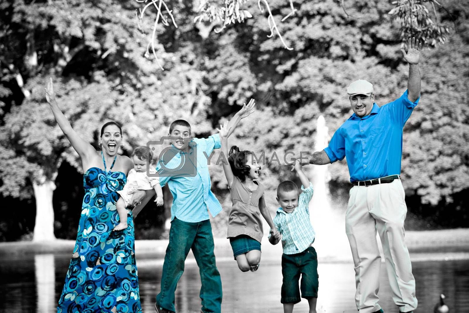 Portrait of a fun young family with four children jumping in the air all at once.  Selective isolated color highlighting the blues.