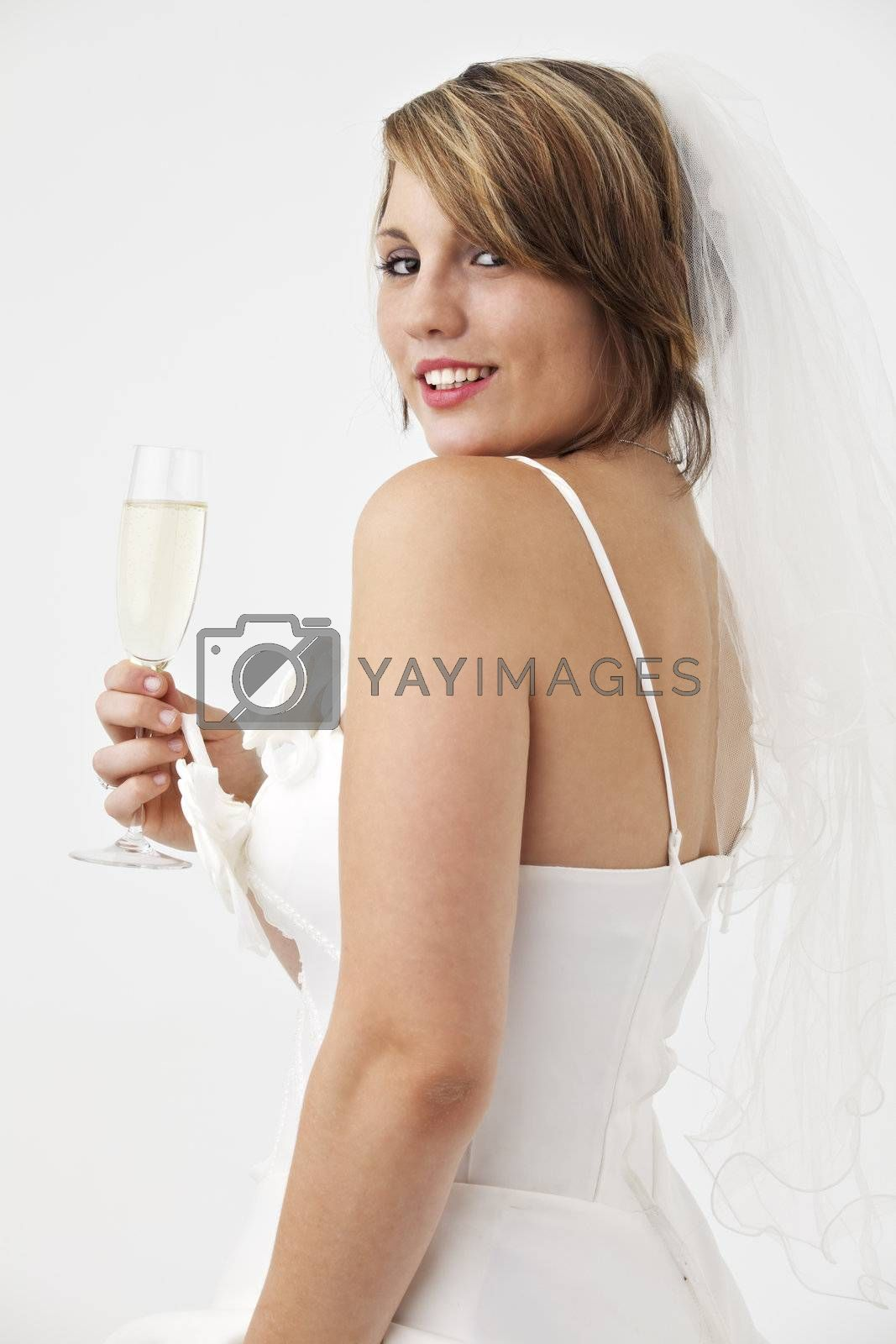 beautiful young bride in a wedding dress with a veil holding a glass of champagne
