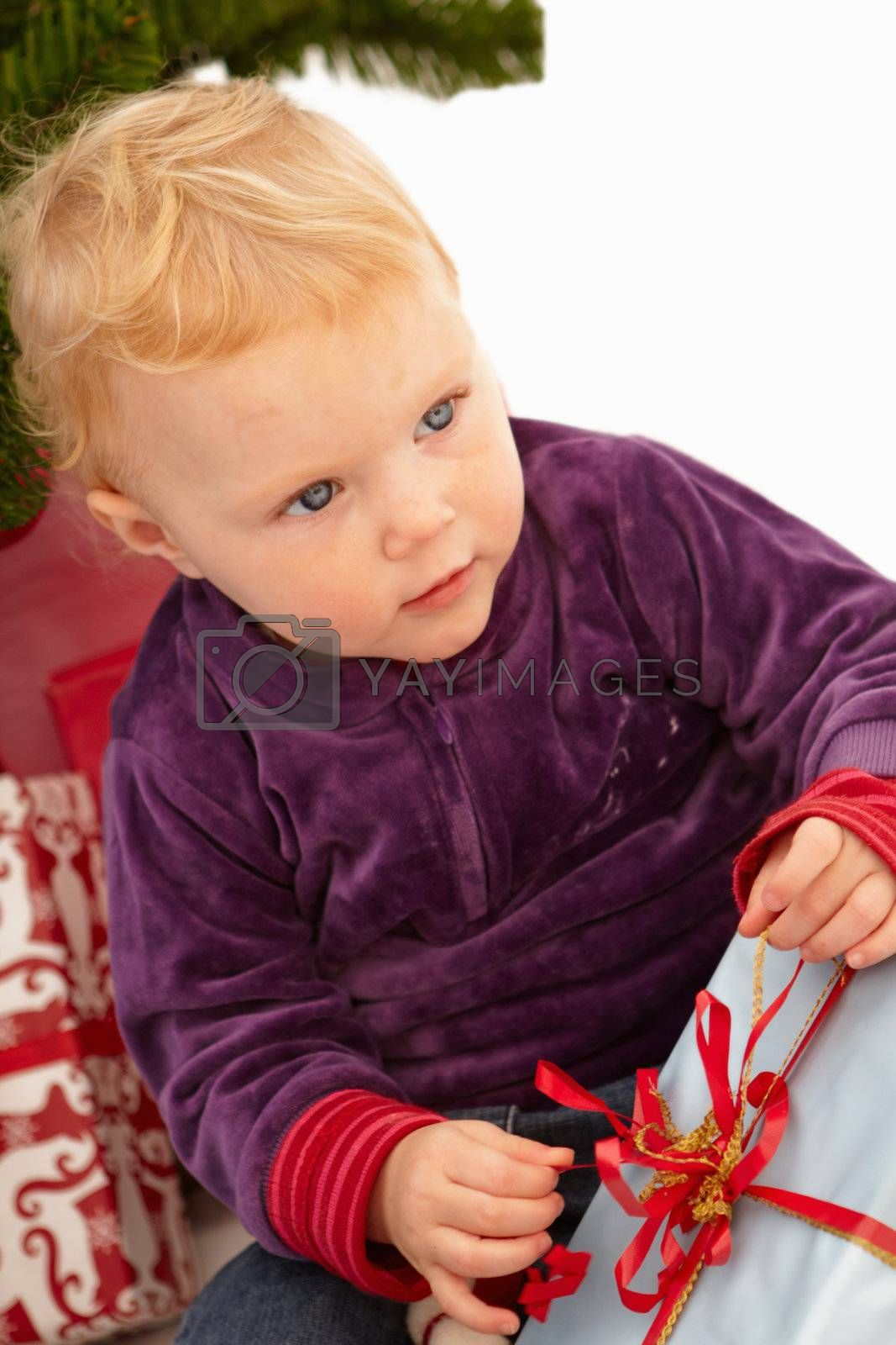 Royalty free image of Christmas - Cute child opening presents by FreedomImage