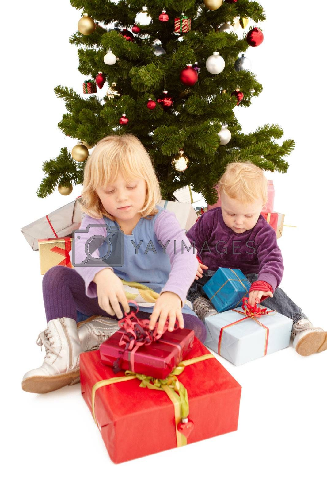 Royalty free image of Christmas - Cute young girls opening their presents by FreedomImage