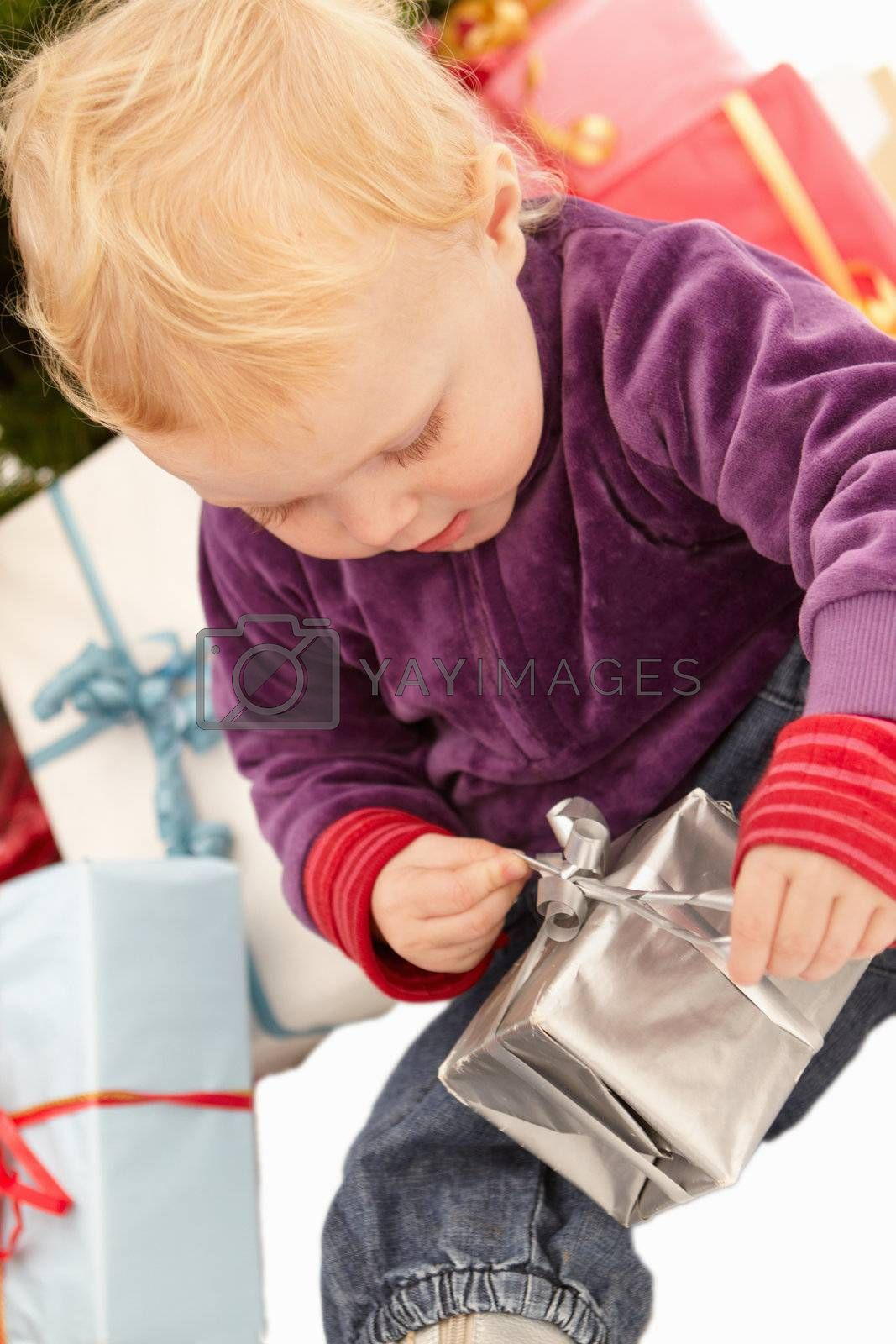Royalty free image of Christmas Presents - Little girl opening gifts by FreedomImage