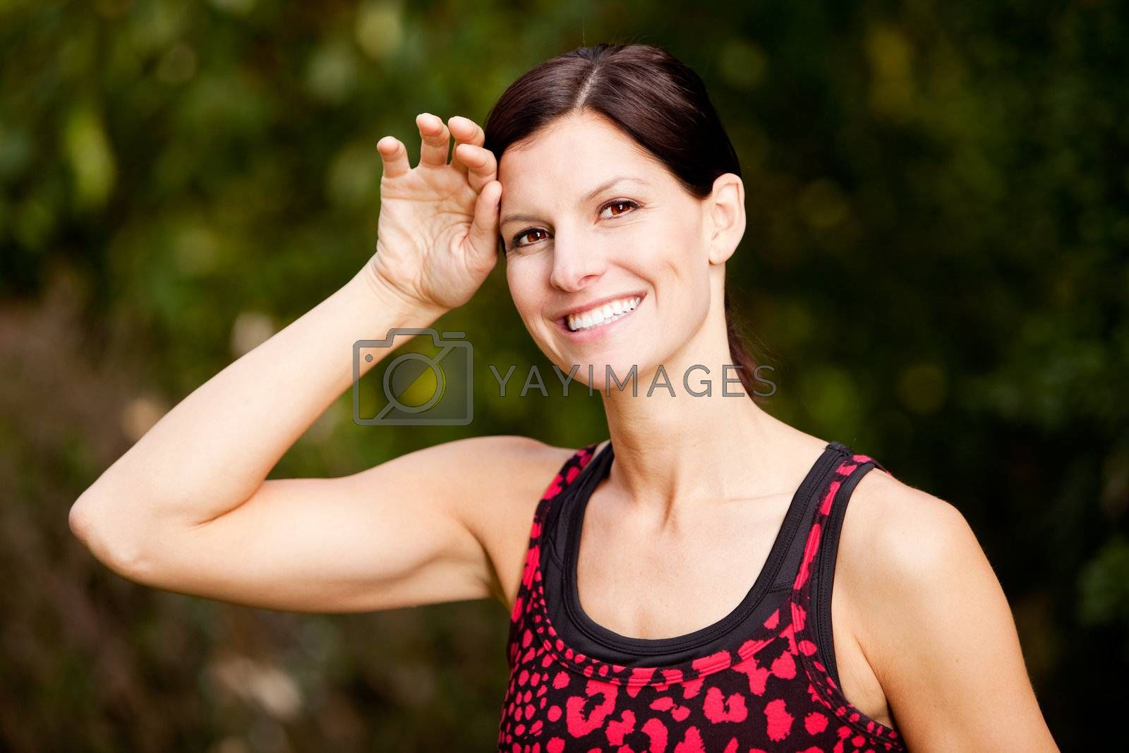A woman exercising in a park, taking a break