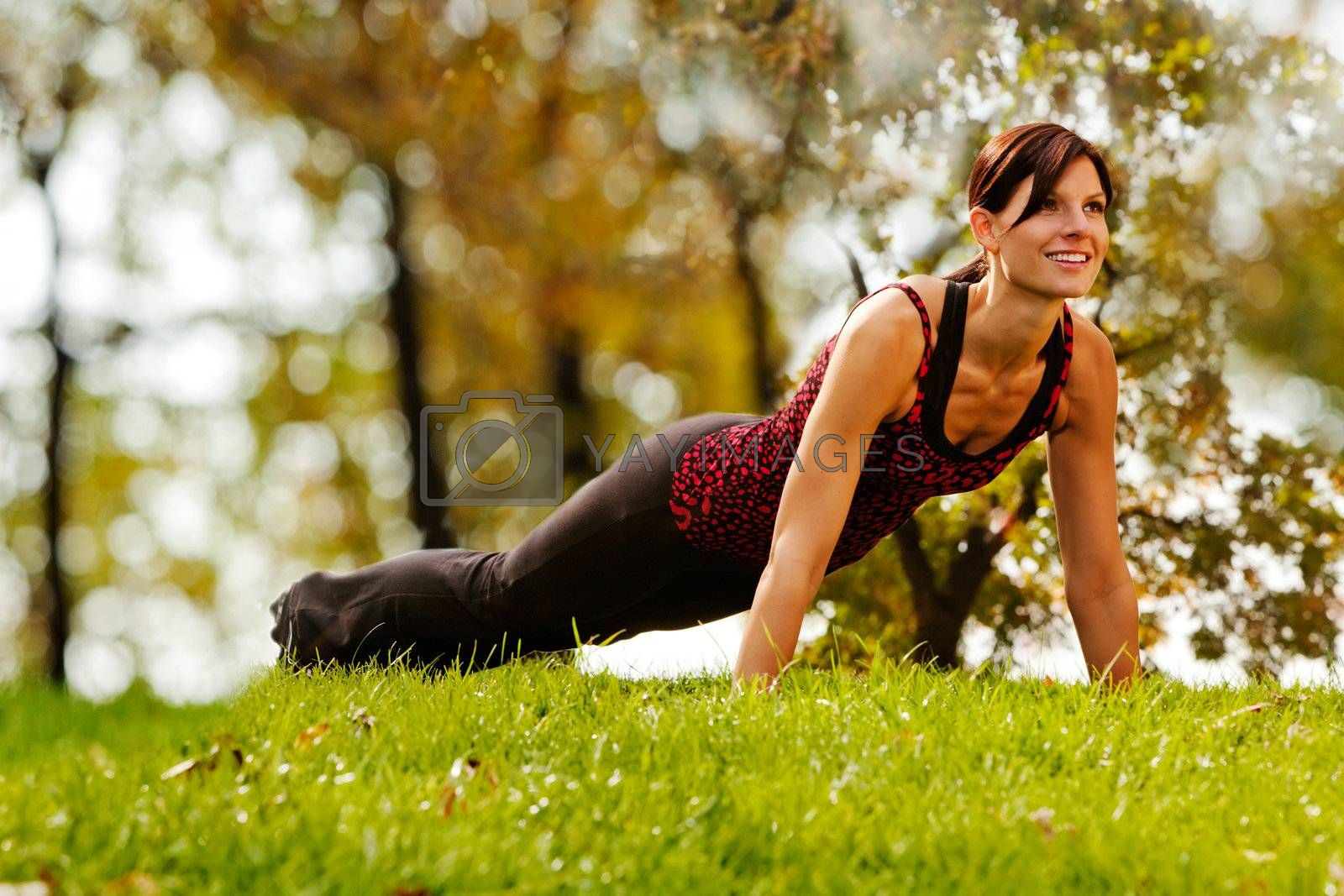 A caucasian female doing push ups in the park