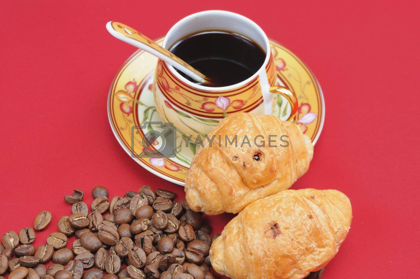 Heap of coffee bean and the cup on a red background