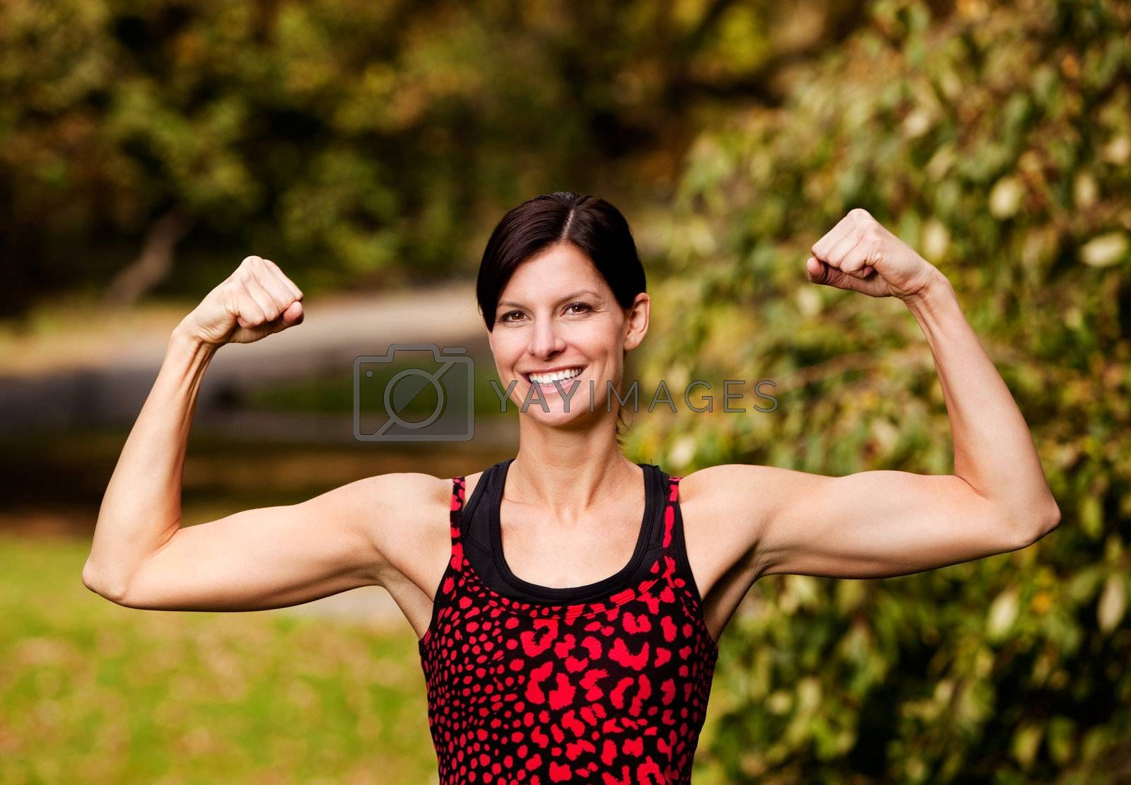 A female fitness model flexing her biceps