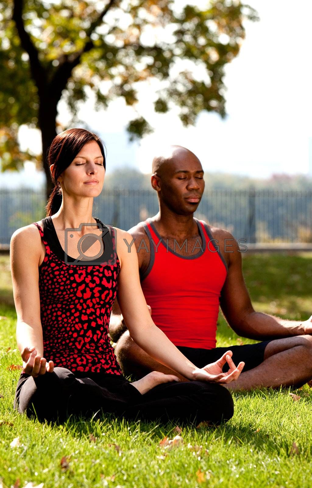 Two people meditating in a city park on a sunny day