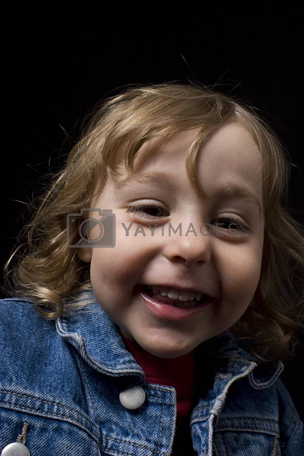 Portrait of a two year old boy wearing a jean jacket laughing