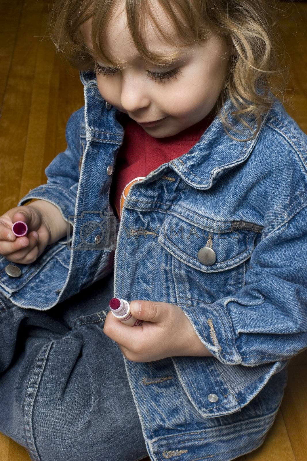 Portrait of a two year old boy wearing a jean jacket with great big smile playing with pink marker sitting on a wood floor