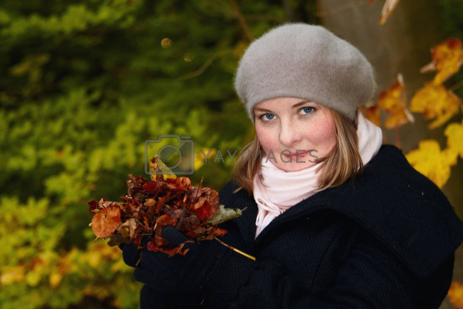 Royalty free image of Autumn - Cute young woman holding leaves by FreedomImage