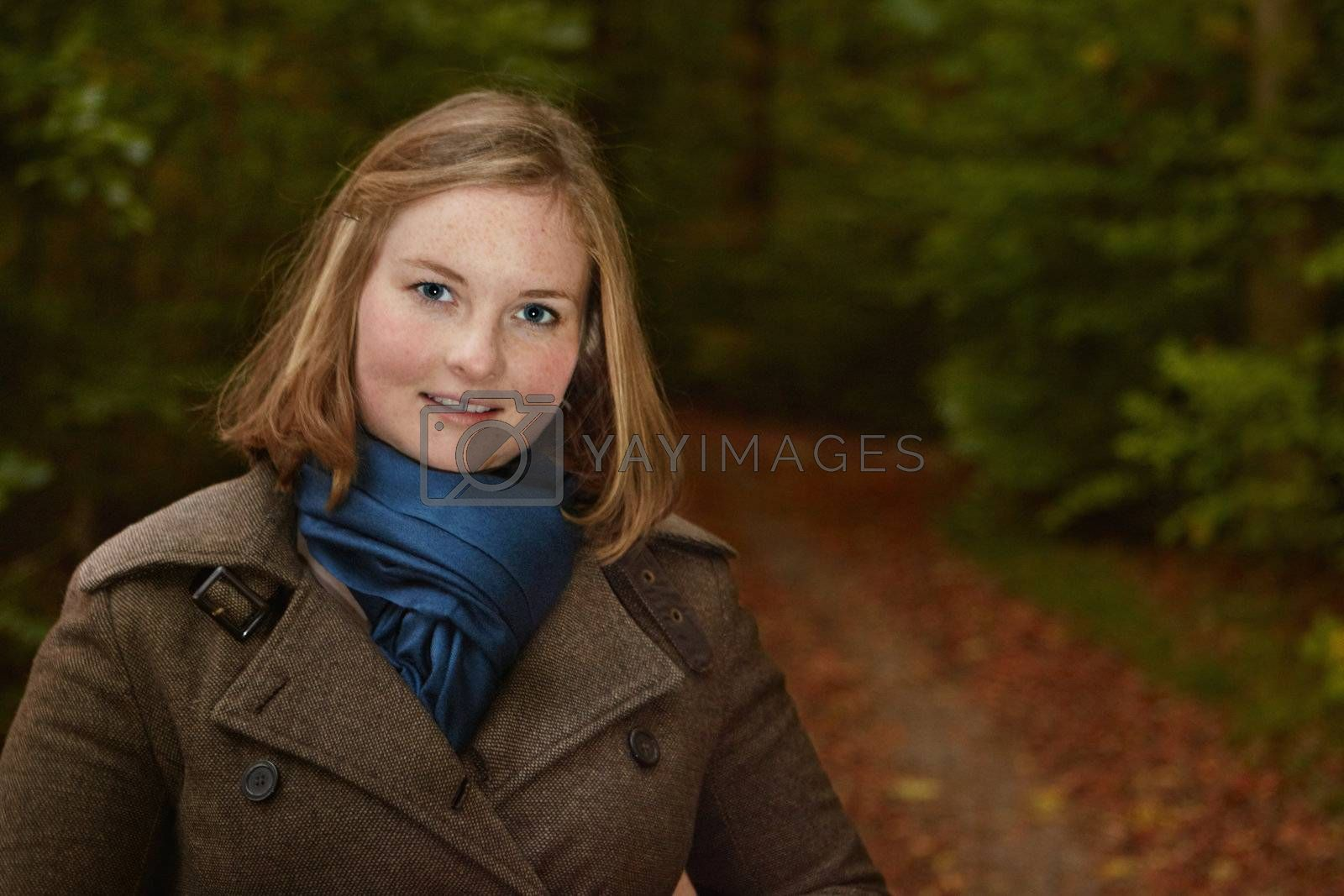 Royalty free image of Freindly young woman standing by a forest path by FreedomImage