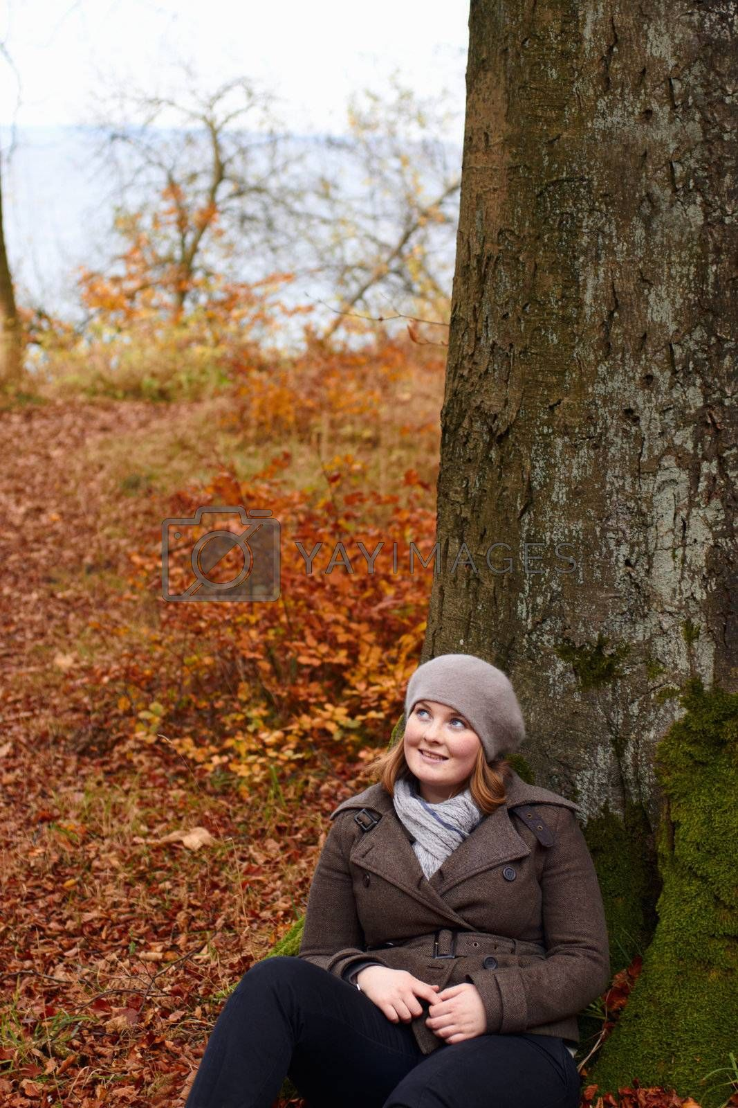 Royalty free image of Fall - Cute young woman looking up at copyspace by FreedomImage